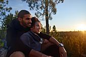 Affectionate hiker couple enjoying sunset in woods