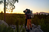 Hiker couple hiking on rock in sunset woods