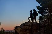 Hiker couple enjoying view of moon at dusk