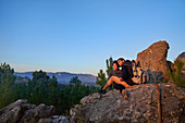 Young hiker couple relaxing and enjoying sunset