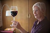 Senior woman enjoying red wine
