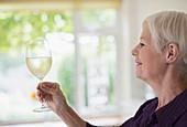 Senior woman drinking white wine