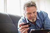 Senior man and credit card using tablet on sofa