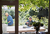 Senior couple gardening and using tablet