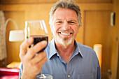Carefree senior man drinking red wine