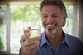 Close up smiling senior man drinking white wine