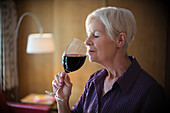 Serene senior woman smelling and tasting red wine