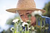 Senior woman smelling flowers in garden