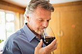 Close up serene man smelling and tasting red wine
