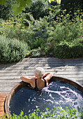 Senior woman relaxing in hot tub on summer patio