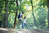 Father and daughter hiking in summer woods