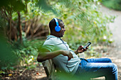 Man relaxing on park bench and smart phone