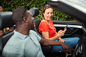 Couple using smart phone in convertible