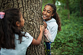 Happy sisters playing at tree trunk in woods