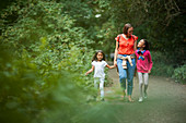 Mother and daughters walking on path in woods