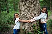 Serene sisters hugging tree trunk in woods