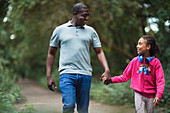 Father and daughter holding hands walking