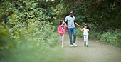 Father and daughters holding hands on path in park