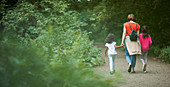 Mother and daughters hiking on path in woods