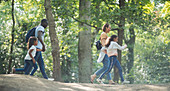 Family hiking past trees in summer woods