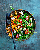 A bowl with fusilli, tomatoes, rocket and feta cheese