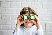 Junge mit zwei Oster-Cupcakes vor den Augen