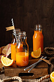 Fresh vitamin juice in small jars (orange and carrot juice)