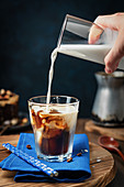 Ice cold coffee with a hand pouring milk
