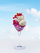 Ice cream sundae with berry ice cream, vanilla ice cream, whipped cream and fresh berries