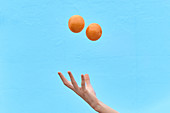 Crop woman tossing fresh orange in air showing concept of healthy diet on blue background