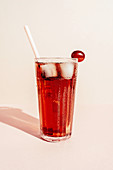 Glass of tasty grape juice in glass placed on pink background