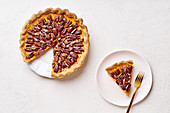 Pecan and pumpkin tart with one slice cut