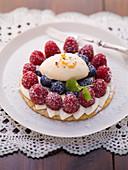 Kleiner Beerenkuchen mit Himbeeren, Heidelbeeren und Eierliköreis