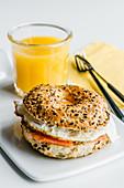 Bagel mit Frischkäse, Lachs und Ei dazu ein Glas Orangensaft