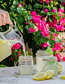 Pouring fresh homemade lemonade from pitcher into glass jars placed on table in blooming summer garden