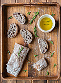 Italian ciabatta bread served on wooden tray with pot of olive oil and fresh rosemary
