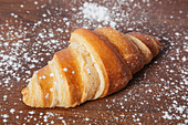 Croissant with golden crust on wooden table with sprinkled with glace sugar