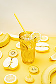 Various fresh fruits arranged on yellow background with glass of cocktail with straw and ice