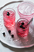Healthy pink beverage decorated with fresh blueberries, bowl with ice cubes