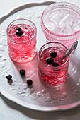 Rosa Getränk mit Blaubeeren und Eiswürfeln