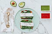 Käse-Spinat-Sandwiches, daneben Avocado- und Tomatensauce