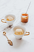 Cups with ice cream bowls, ornamental spoon and jar of peanut butter on marble table
