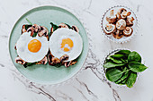 Fried eggs placed of sandwiches with mushrooms and spinach on plate on marble table