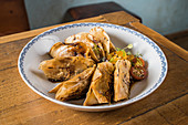 Plate with traditional Asian gyozas filled with vegetables and served with Sriracha hot sauce with mustard and soy