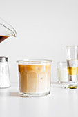 Iced coffee latte served in glass cup on white table with cup of milk and glassware