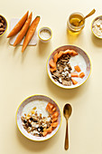 Bowls with delicious healthy breakfast prepared with yogurt and granola with fresh cantaloupe melon served on table with ingredients