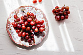Ornamental plate with ripe red grapes placed near bunch of grape on white table