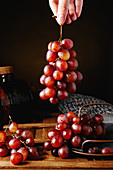 Taking bunch of fresh juicy red grapes from tray placed on wooden table