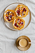 Tarts made of filo dough and filled with sliced fruits served with cup of aromatic coffee with milk