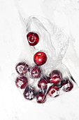 Ripe red cherry berries in transparent plastic sack placed on white table